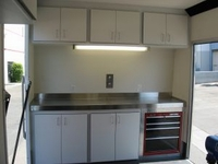Front stainless steel work bench with over head storage cabinets and lighting
